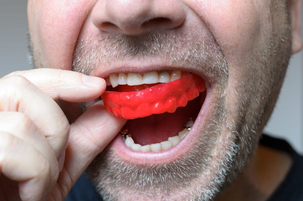 Man inserting a red mouth guard into his mouth