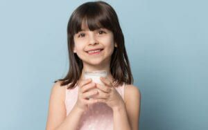 Child smiling and holding a glass of milk